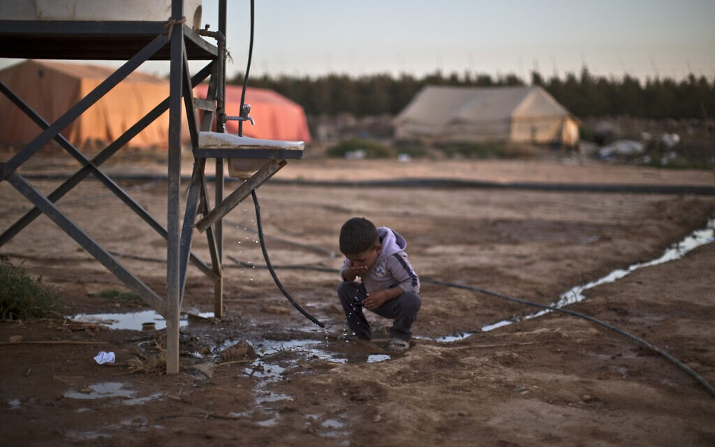 ילד במחנה פליטים בירדן שותה מים (צילום: AP Photo/Muhammed Muheisen)