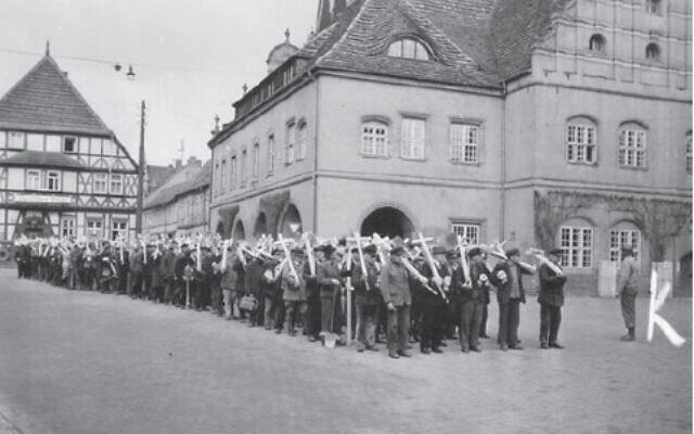 תושבי גרדלגן שבגרמניה התכנסו בהנחיית הצבא האמריקאי בכיכר העיר כדי לצעוד לבית העלמין הסמוך על מנת לטעת צלבים במקום (צילום: Stiftung Gedenkstätten Buchenwald und Mittelbau-Dora National Archives Records Administration)