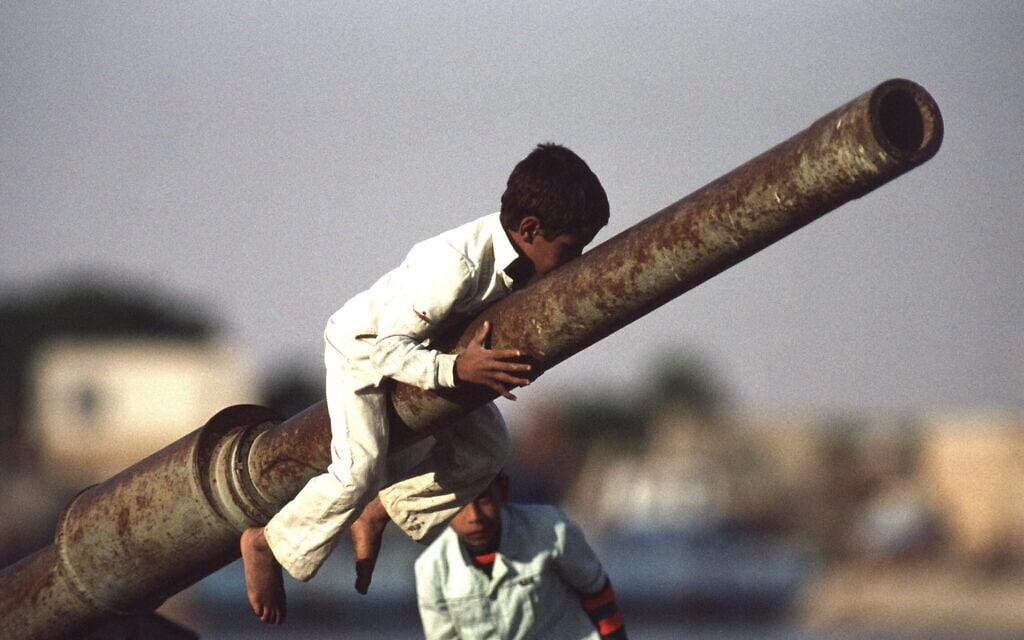 1990: ילדים מצרים משחקים על שרידי טנק בדרום תעלת סואץ (צילום: Barry Iverson / Alamy)