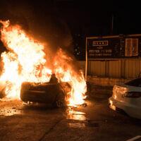 מכונית עולה באש בפרעות שהתרחשו בעכו ב-12 במאי 2021 (צילום: רוני עופר/פלאש90)