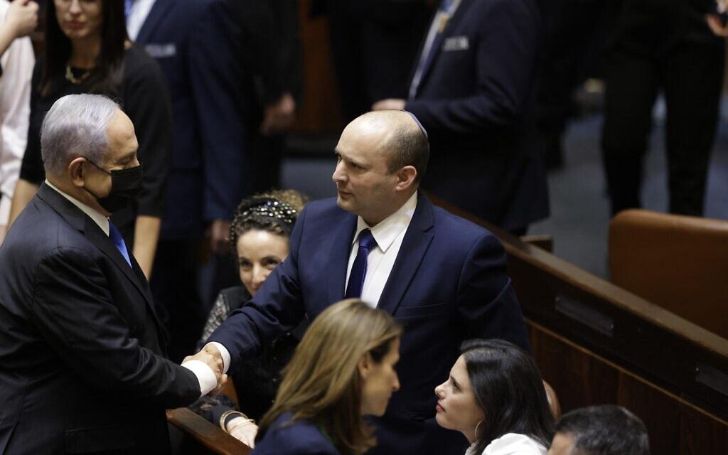 נפתלי בנט לוחץ את ידו של בנימין נתניהו אחרי השבעת הממשלה ה-36 בכנסת, 13 ביוני 2021 (צילום: אוליבייה פיטוסי/פלאש90)