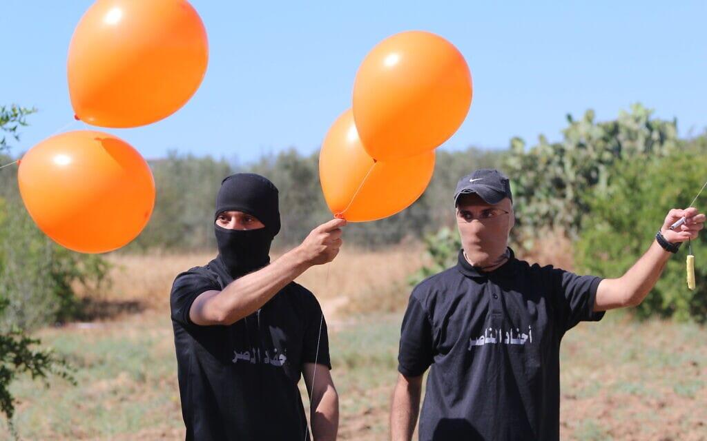 פלסטינים רעולי פנים מהג'יהאד האסלאמי מכינים בלוני תבערה מזרחית לעיר עזה, 15 ביוני 2021 (צילום: Atia Mohammed/FLASH90)