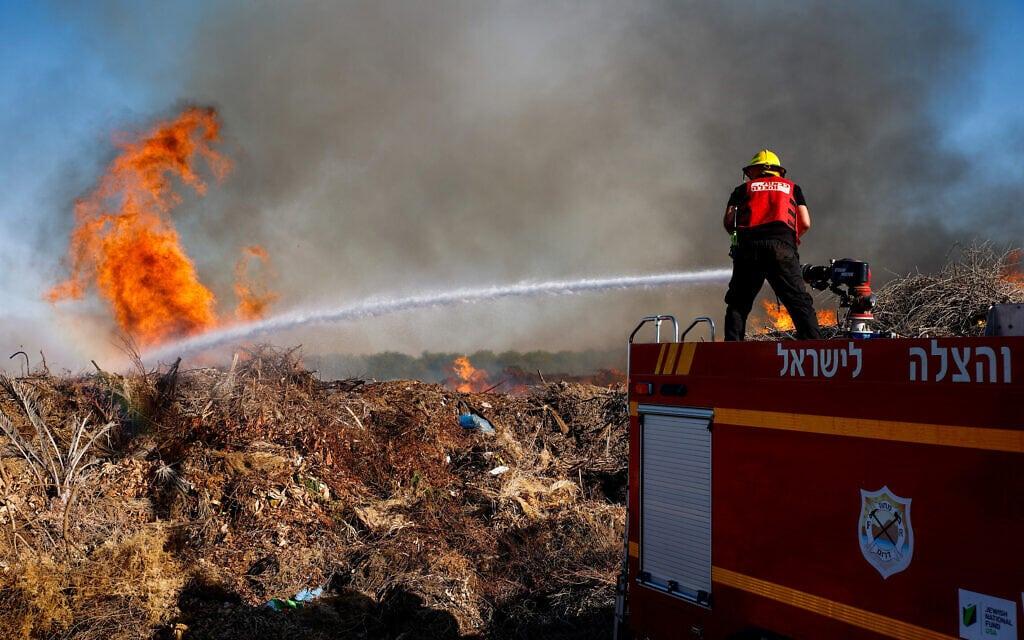 לוחמי אש מכבים שרפה שנגרמה מבלוני תבערה ביער שמחוני בעוטף עזה, 15 ביוני 2021 (צילום: פלאש90)