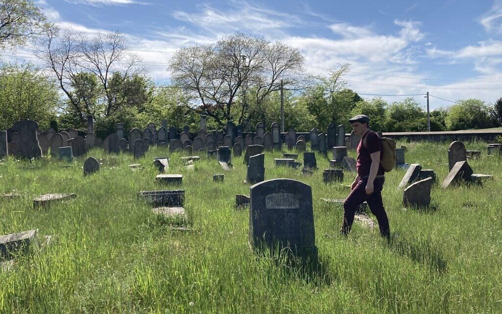 מתיאש קיראי בין המצבות שהושחתו בבית הקברות היהודי העתיק בנאג'יטטני. 11 במאי 2021 (צילום: יעקב שוורץ)