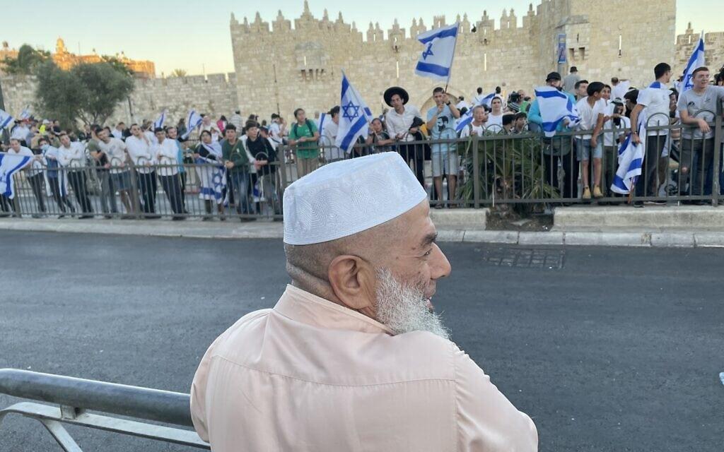 תושב מזרח ירושלים משקיף מהעבר השני של הרחוב מול שער שכם על משתתפי צעדת הדגלים, 15 ביוני2021 (צילום: אמיר בן-דוד)
