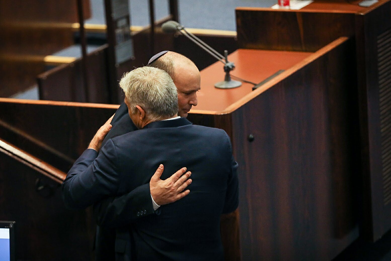 נפתלי בנט יורד מדוכן הנאומים ומתחבק עם יאיר לפיד שעולה לנאום, בישיבת אישור הממשלה ה-36. 13 ביוני 2021 (צילום: דוברות הכנסת / נועם מושקוביץ)
