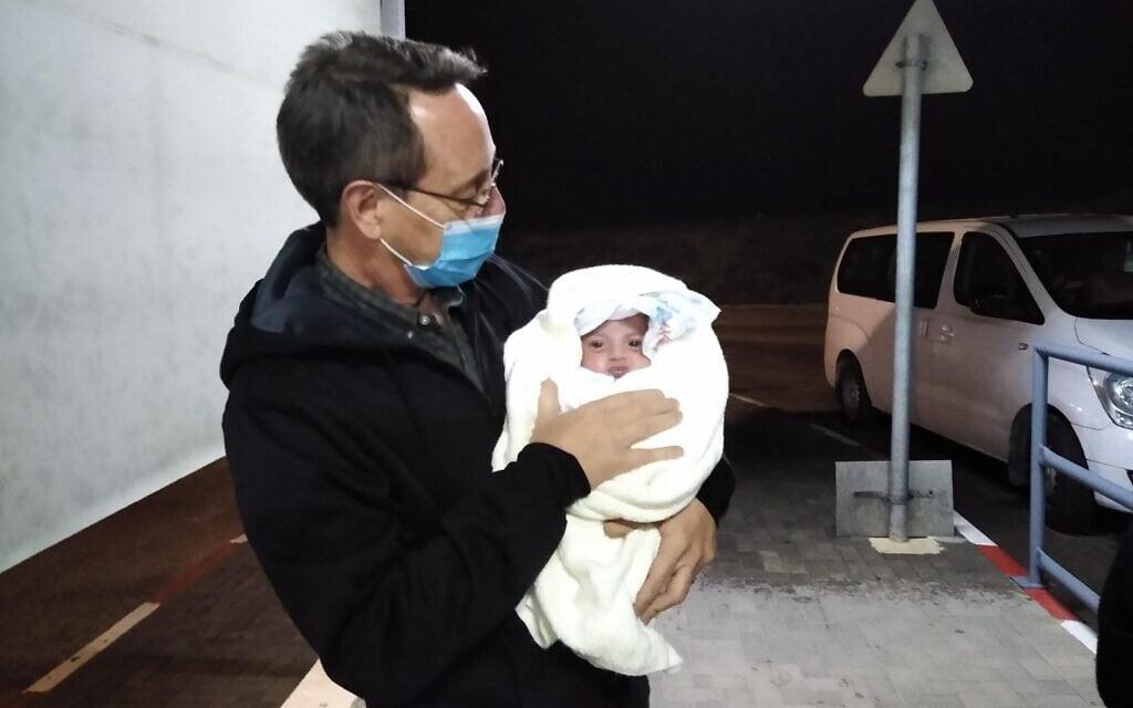 """יונתן מיילס עם תינוק שעבר טיפול בישראל (צילום: באדיבות """"שבת אחים"""")"""