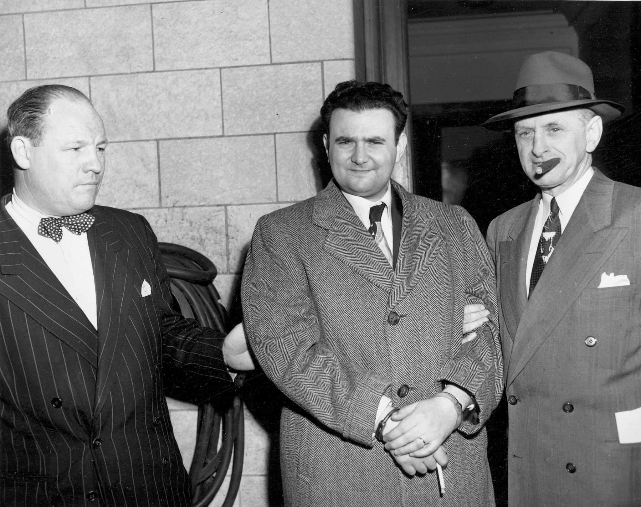 דייוויד גרינגלאס האזוק מלווה על ידי המרשל יוג'ין פיצג'רלד מבית המשפט הפדרלי בניו יורק אחרי שנידון ל-15 שנות מאסר, 6 באפריל 1951 (צילום: AP)