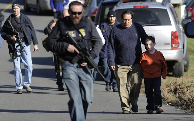 הורים עוזבים יחד עם ילדיהם את אזור ההיערכות לאחר שהתאחדו עם ילדיהם, שניצלו מהירי בבית הספר היסודי סנדי הוק בניוטאון שבקונטיקט, 14 בדצמבר 2012 (צילום: AP Photo/Jessica Hill, File)