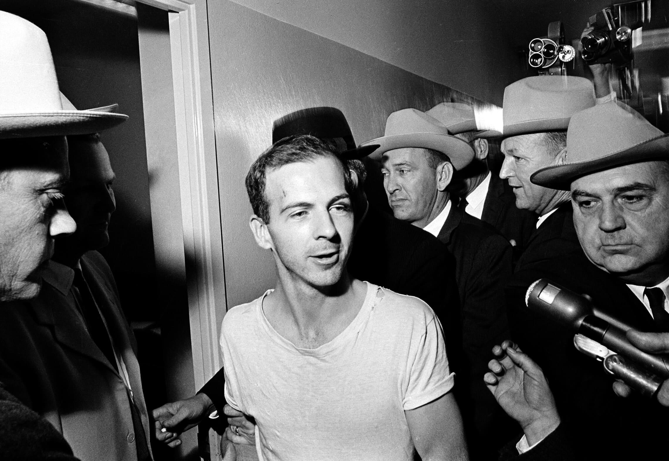 לי הארווי אוסוולד מוקף בשוטרים כשהוא מובל במסדרונות תחנת המשטרה בדאלאס לחקירה יום למחרת ההתנקשות בנשיא ג'ון קנדי, 23 בנובמבר 1963 (צילום: AP Photo)