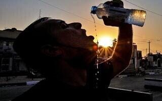 עובד בתחנת דלק בבצרה, עיראק, שותה מים, יולי 2020 (צילום: AP Photo/Nabil al-Jurani)