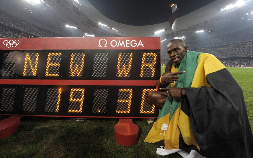 יוסיין בולט עם צג הזמן המראה ששבר את שיא העולם בריצת 200 מטר, באולימפיאדת בייג'ינג, 2008 (צילום: AP Photo/Thomas Kienzle)