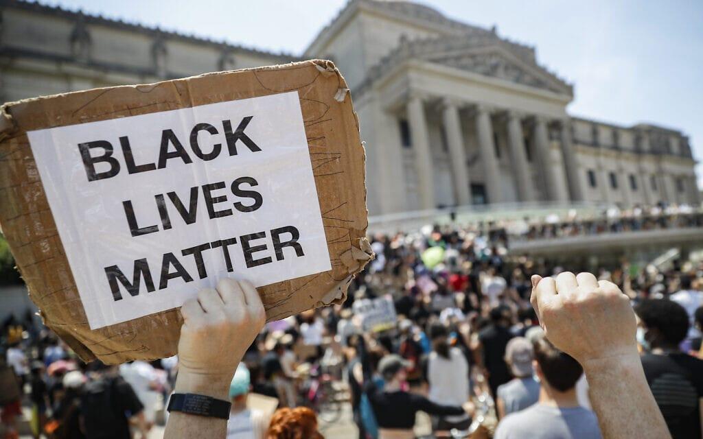 """מפגין מניף שלט שעליו נכתב """"חיי שחורים חשובים"""" בהפגנה ברובע ברוקלין שבניו יורק, 19 ביוני 2020 (צילום: AP Photo/John Minchillo, File)"""