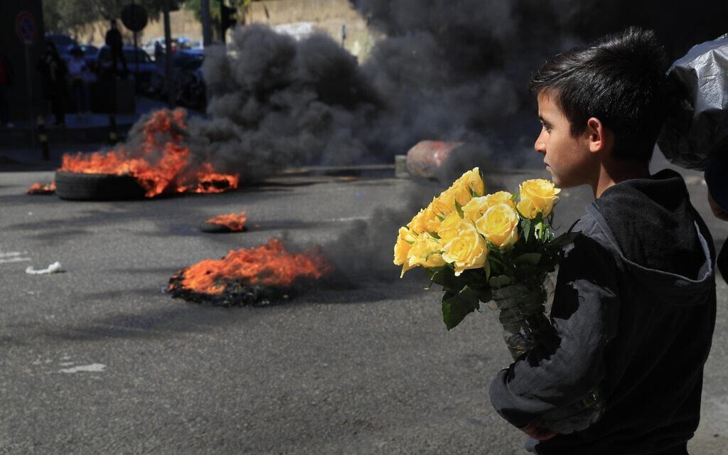 ילד מוכר פרחים מביט לעבר המפגינים ששורפים צמיגים במחאה על עליית המחירים והתרסקות הכלכלה הלבנונית, ביירות, 16 במרץ 2921 (צילום: AP Photo/Hussein Malla)