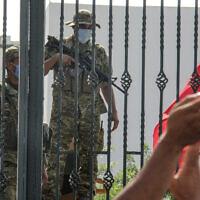 הצבא התוניסאי שומר על בניין הפרלמנט, ומפגינים מקיפים את הבניין בהזדהות.26.7.2021 (צילום: AP Photo/Hedi Azouz)
