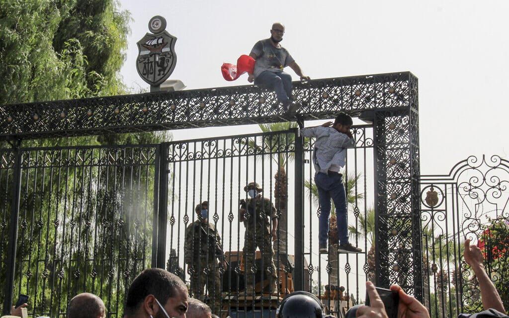 חיילים תוניסאים שומרים על הכניסה לפרלמנט בזמן שמפגינים מטפסים על הגדרות, 26 ביולי 2021 (צילום: AP Photo/Hedi Azouz)