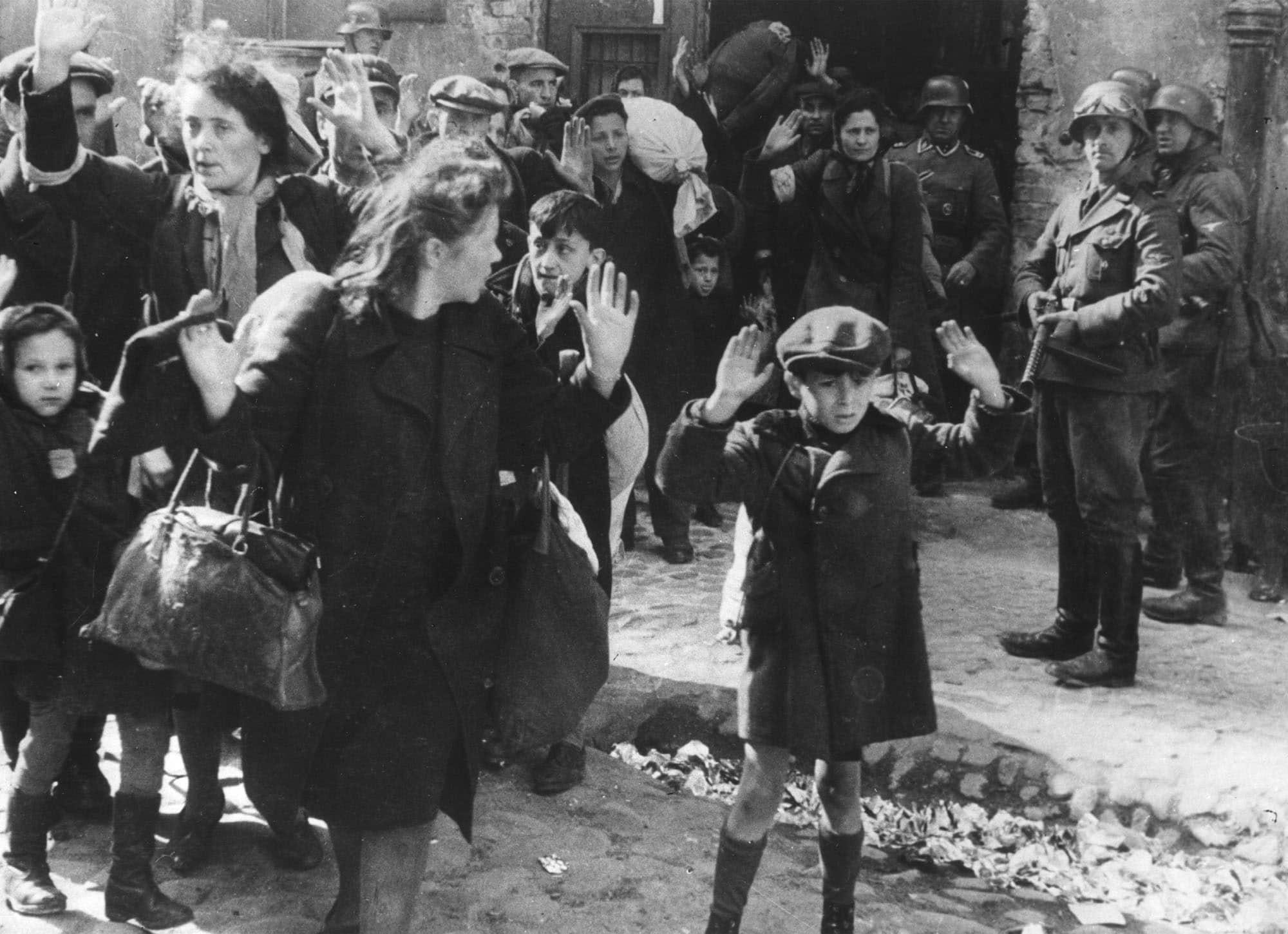התמונה המפורסמת מגטו ורשה: קבוצת יהודים, בהם נער צעיר, מלווים אל מחוץ לגטו ורשה על ידי חיילי הצבא הגרמני, ב-19 באפריל 1943 (צילום: AP Photo/B.I. Sanders)