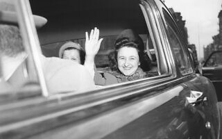 אתל רוזנברג מחייכת ומנופפת בידה כשהיא עוזבת את בית המעצר לנשים בניו יורק, בדרכה לתא הנידונים למוות, 11 באפריל 1951 (צילום: Murray Becker, AP)