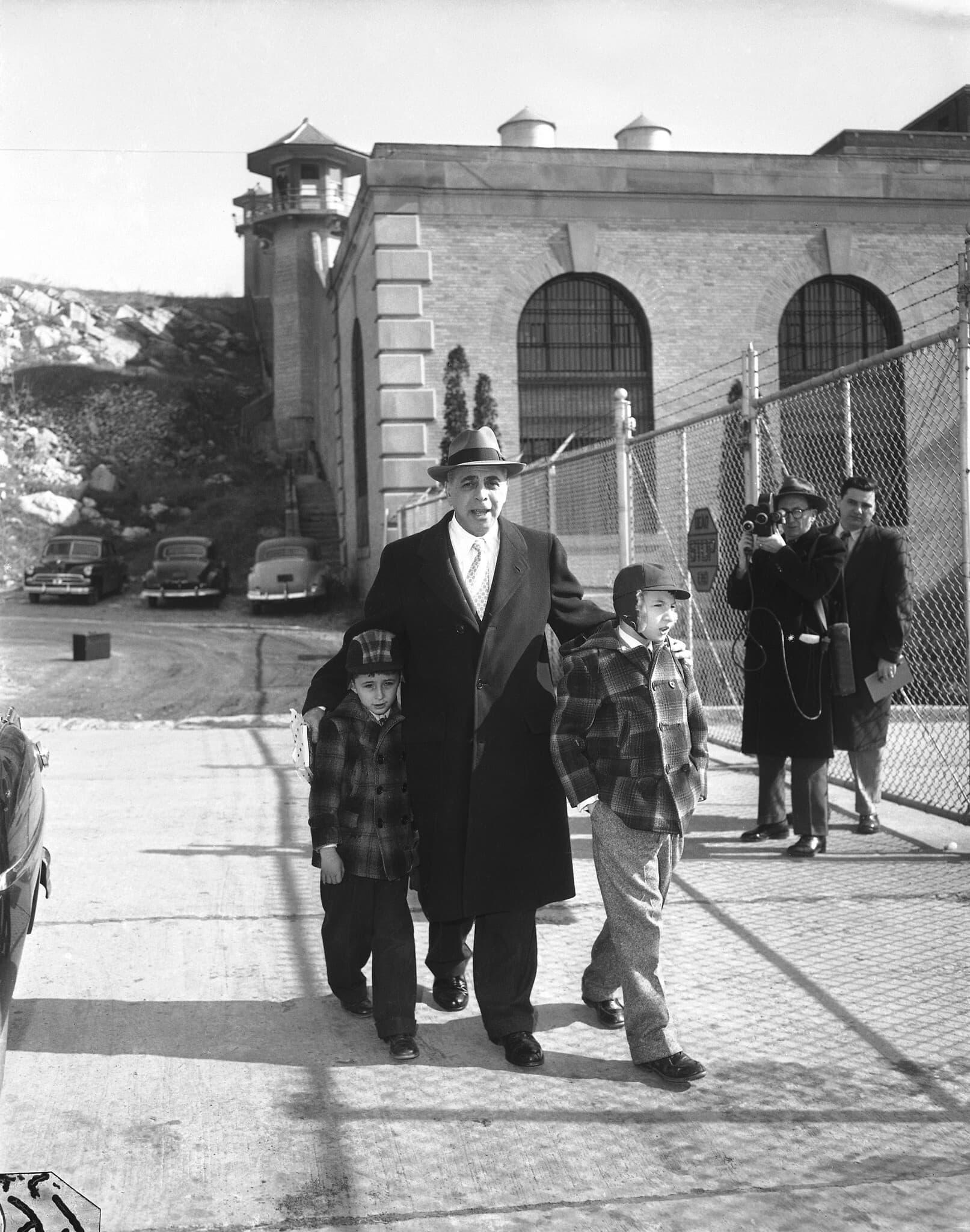 רוברט רוזנברג, בן 5 בתמונה, ואחיו מייקל, 9, מלווים על ידי עורך הדין עמנואל בלוך לבית הכלא סינג סינג בניו יורק ב-14 בפברואר 1953, כדי לבקר את הוריהם, יוליוס ואתל רוזנברג (צילום: John Lindsay, AP)