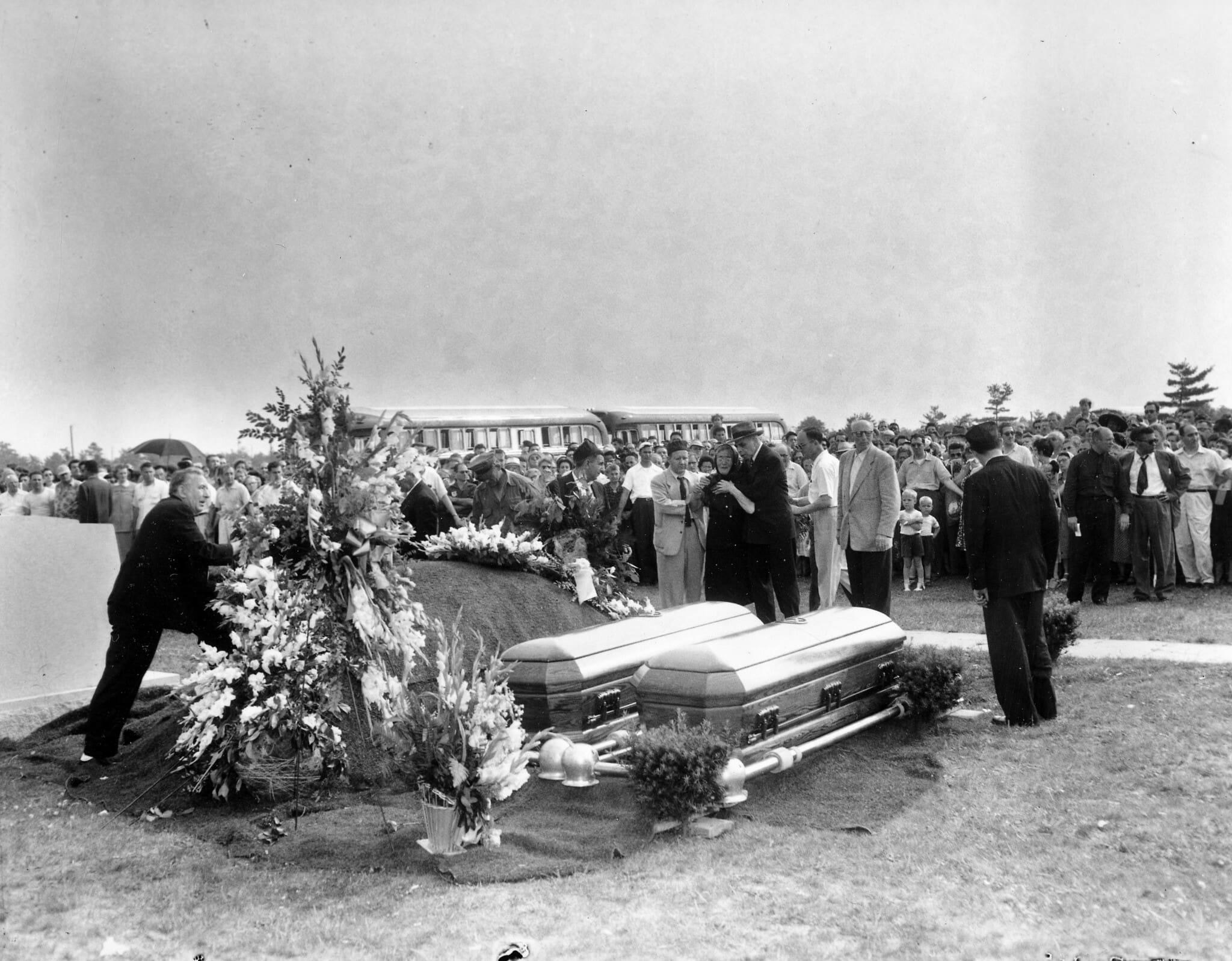 פרקליט ההגנה עמונאל בלוך, מנחם את סופי רוזנברג בזמן שהיא מביטה על ארונות הקבורה של בנה וכלתה, יוליוס ואתל רוזנברג, במהלך טקס הלוויה שלהם בלונג איילנד, 21 ביוני 1953 (צילום: AP)