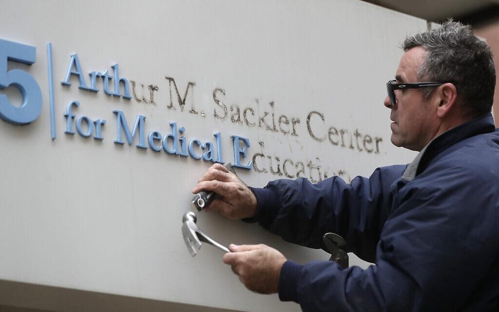 שמו של ארתור סאקלר מוסר מהשלט בכניסה לבית הספר לרפואה טאפטס שבבוסטון, 5 בדצמבר 2019 (צילום: Steven Senne, AP)