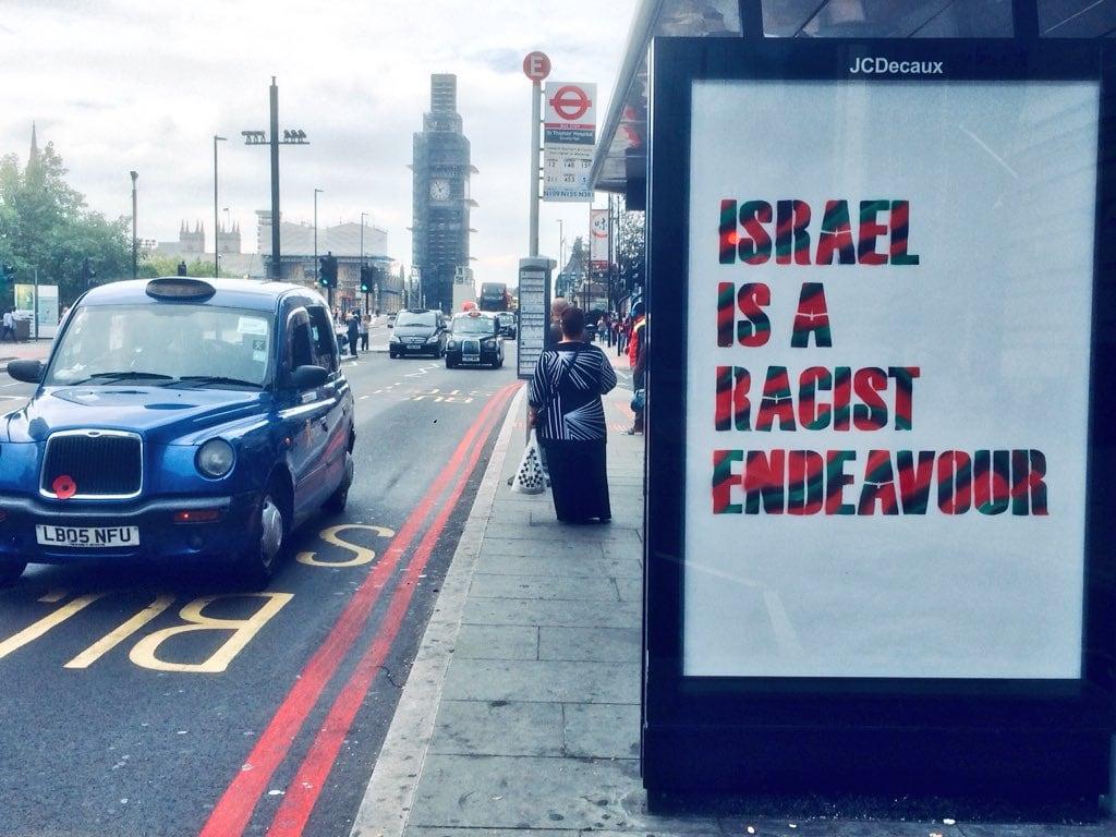 """תחנת אוטובוס בלונדון שהושחתה בכרזה בלתי חוקית ועליה הכתובת """"ישראל היא פרויקט גזעני"""", שתלתה קבוצה פרו-פלסטינית במחאה על כך שמפלגת הלייבור הבריטית אימצה את הגדרת האנטישמיות של כוח המשימה הבינלאומי להנצחת זכר השואה , 6 בספטמבר 2018 (צילום: טוויטר)"""