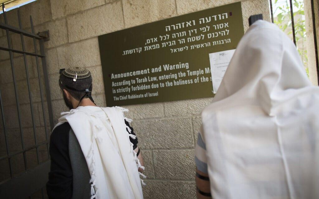 יהודים מתפללים מחוץ לשערי הר הבית, לצד שלט הרבנות הראשית האוסר על תפילה בשטחי הר הבית (צילום: יוסי זמיר/פלאש90)
