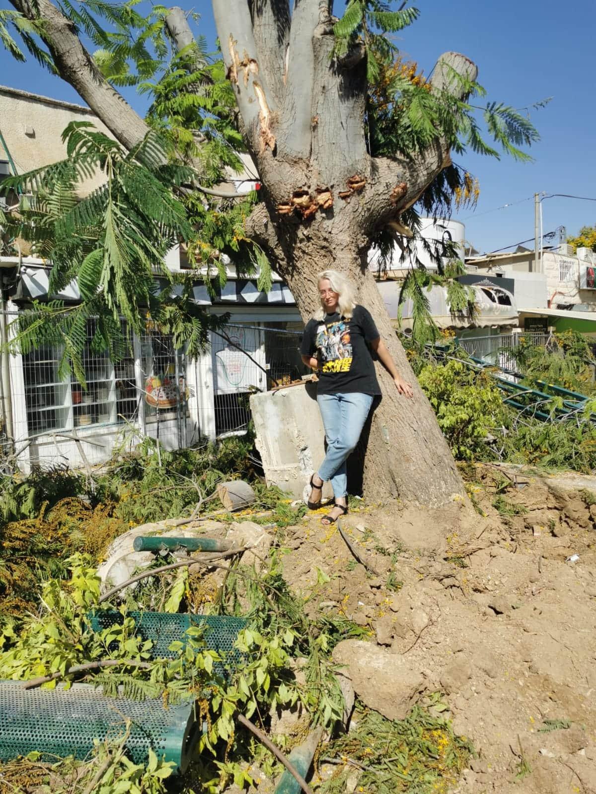 """רות השקס נשענת על עץ שעדיין לא נכרת ברחוב קק""""ל בבאר שבע (צילום: שיר פריימן)"""
