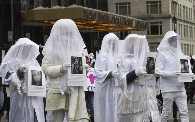 מפגינים נושאים תמונות של קורבנות נשק בברית מצעד הנשים בניו יורק, 19 בינואר 2019 (צילום: Mary Altaffer, AP)