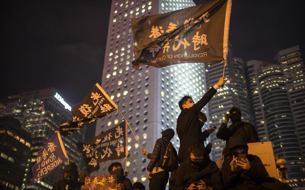 """מפגינים בהונג קונג מניפים דגלים עם הסלוגן """"מהפכה עכשיו"""",12 בדצמבר 2019 (צילום: AP Photo/Mark Schiefelbein)"""