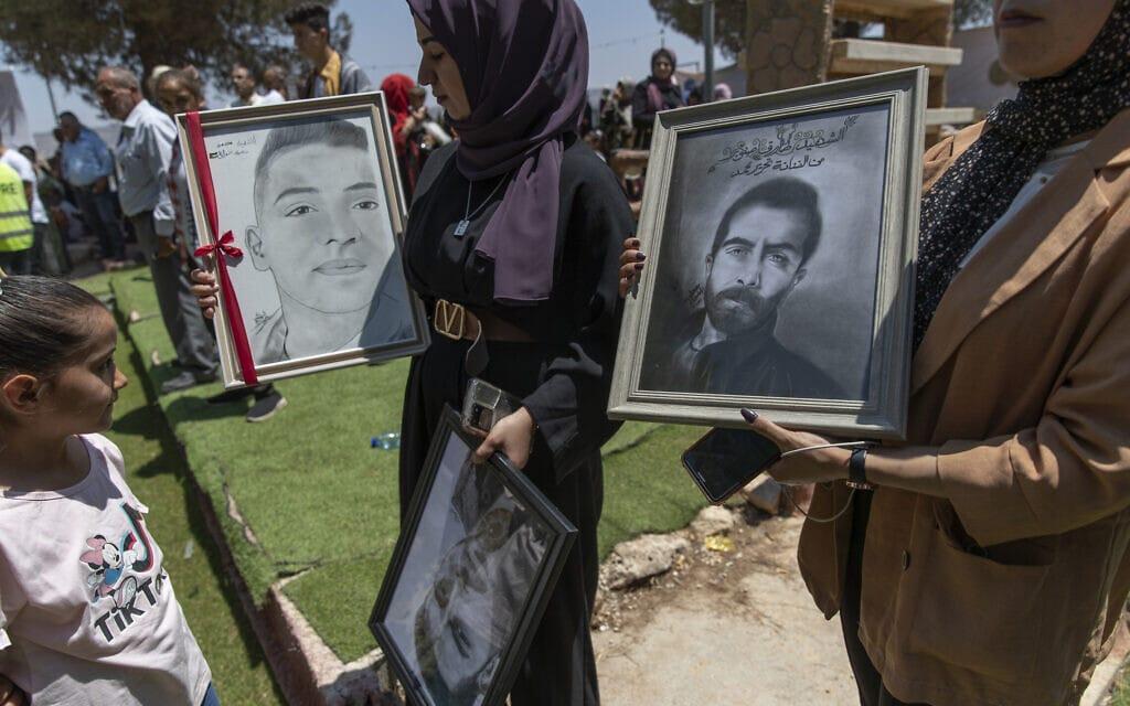 מפגינים פלסטינים נושאים תמונות של הרוגים בהפגנות. (צילום: AP Photo/Nasser Nasser)