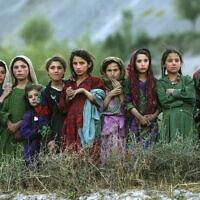 """נערות אפגניות צופות בעובדי האו""""ם והצבא האמריקאי, 4 באוקטובר 2004 (צילום: AP Photo/Emilio Morenatti)"""