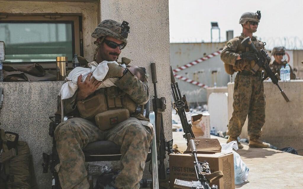 חייל מארינס אמריקאי מטפל בתינוק אפגני במהלך פינוי אפגניסטן, 20 באוגוסט 2021 (צילום: Sgt. Isaiah Campbell/U.S. Marine Corps via AP)
