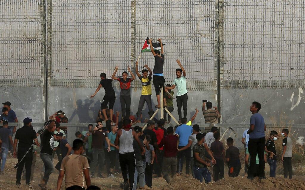 מפגינים מטפסים על הגדר בגבול עזה-ישראל, 21 באוגוסט 2021 (צילום: AP Photo/Adel Hana)