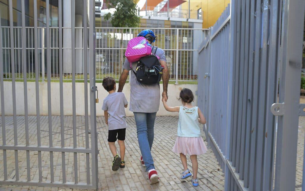 אב לוקח את ילדיו לגן בתל אביב, 18 באוקטובר 2020 (צילום: אבשלום ששוני/פלאש90)