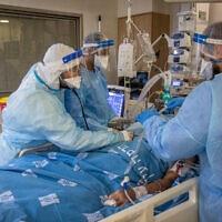 אנשי צוות במחלקת הקורונה של בית החולים הדסה עין כרם מטפלים בחולה, 25 באוגוסט 2021 (צילום: יונתן זינדל, פלאש 90)