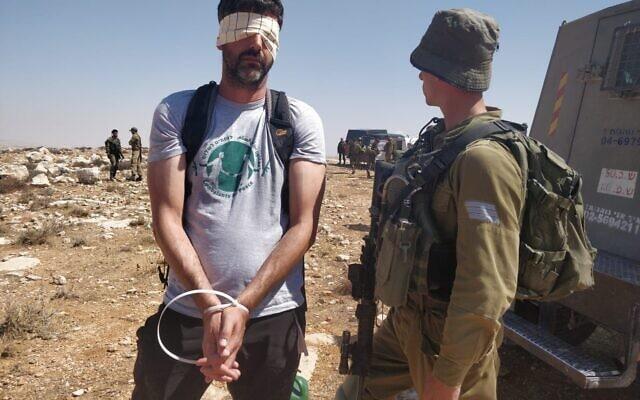 """אחד הפעילים, ממייסדי """"לוחמים לשלום"""", אבנר וישניצר, מעוכב ועיניו מכוסות בפלנלית. (צילום: דפנה בנאי)"""