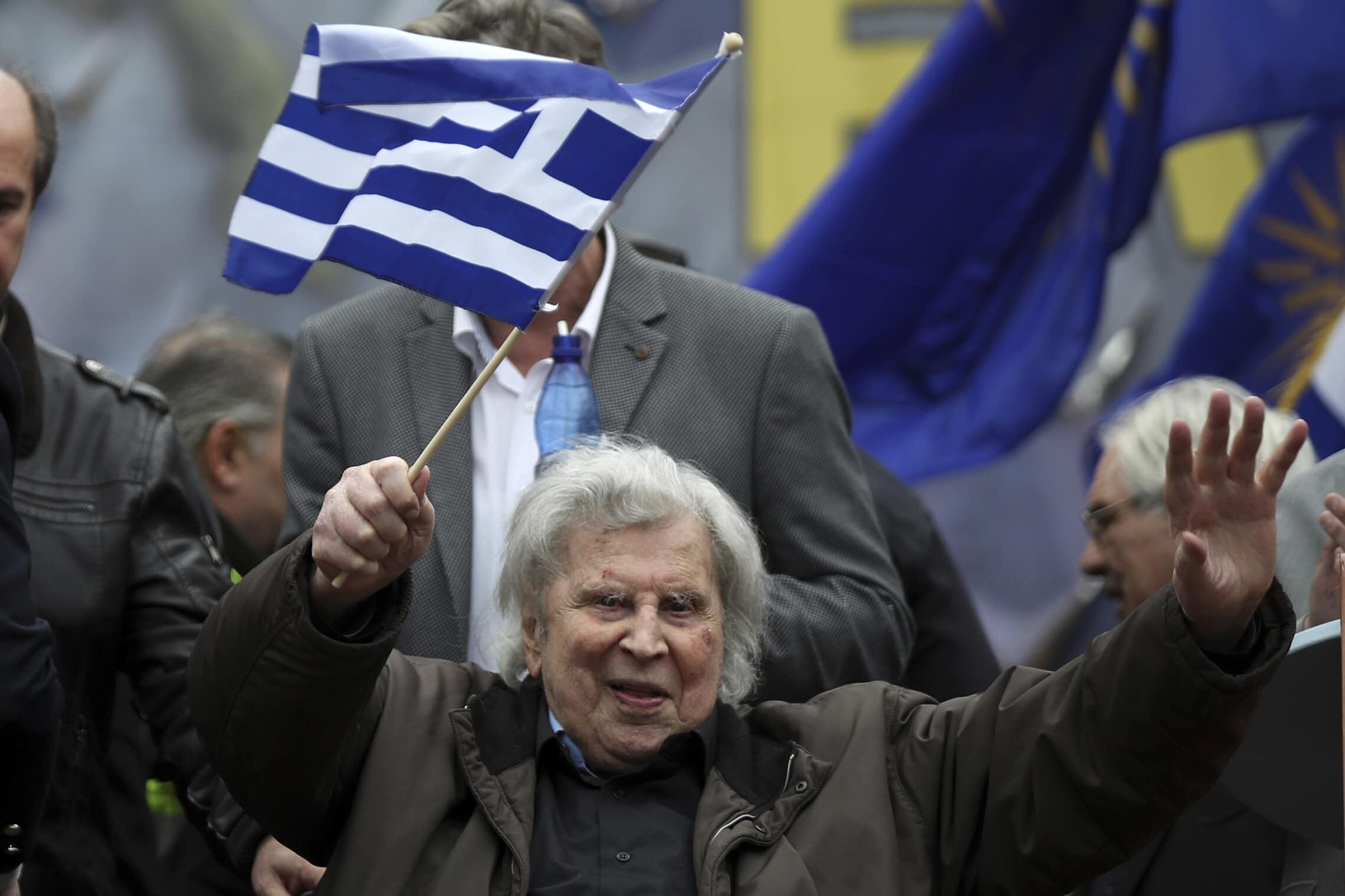 מיקיס תאודוראקיס מנופף בדגל יוון לעבר ההמון בעצרת באתונה, 4 בפברואר 2018 (צילום: AP Photo/Petros Giannakouris)