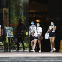 עוברי אורח בסינגפור עוטים מסכות על פניהם, 10 באפריל 2020 (צילום: AP Photo/Yong Teck Lim, File)