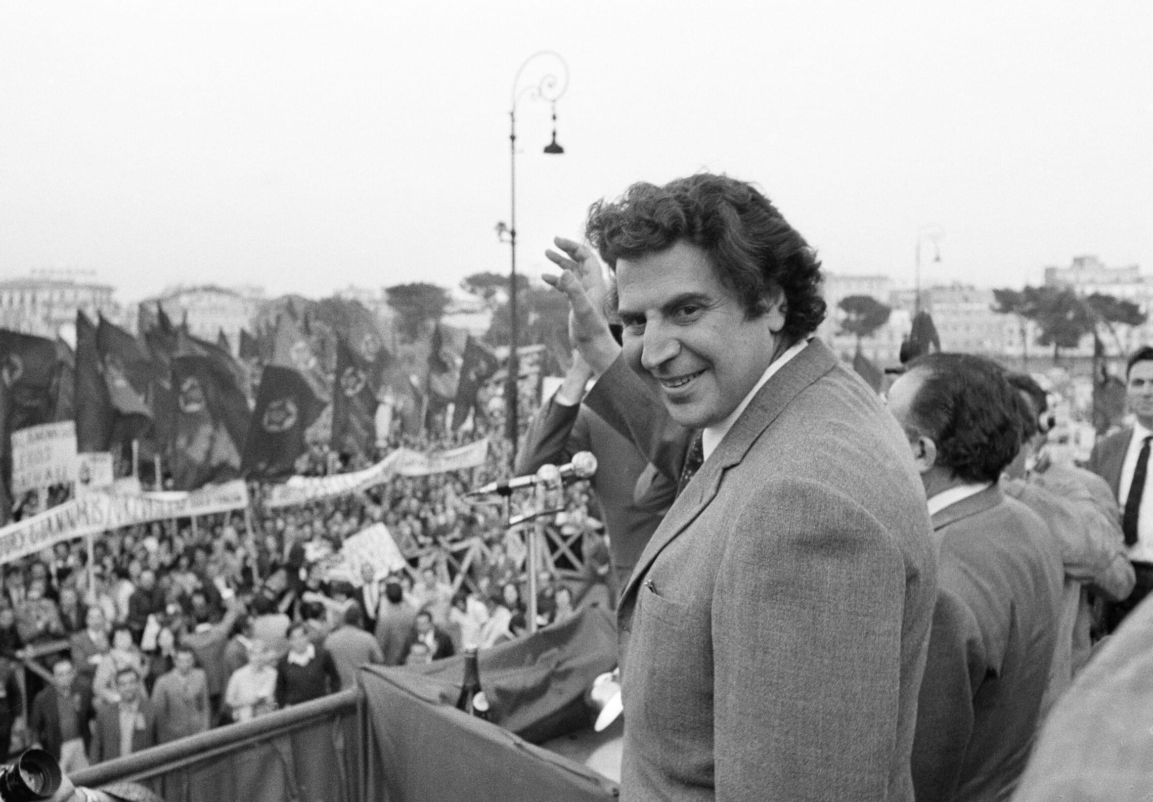 """מיקיס תאודוראקיס מנופף לקהל בעצרת נגד נאט""""ו שארגנה המפלגה הקומוניסטית האיטלקית ברומא, 27 במאי 1970 (צילום: AP Photo)"""