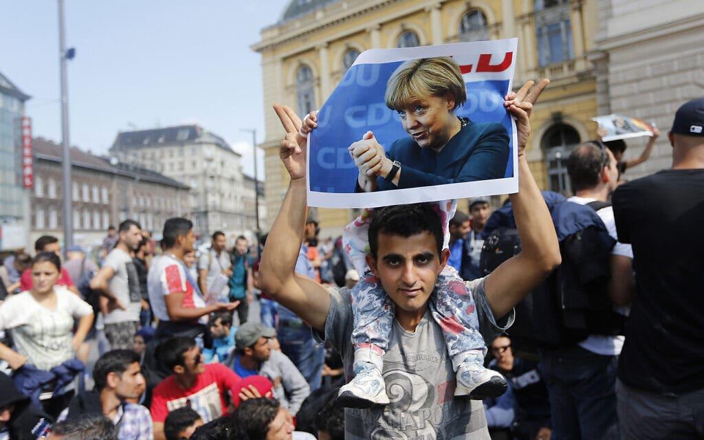 מהגר נושא שלט עם תמונת אנגלה מרקל ב4 בספטמבר 2014, בצעדה מבודפסט, הונגריה, לאוסטריה, לציון מדיניותה מסבירת הפנים למהגרים. (צילום: AP Photo/Frank Augstein, file)