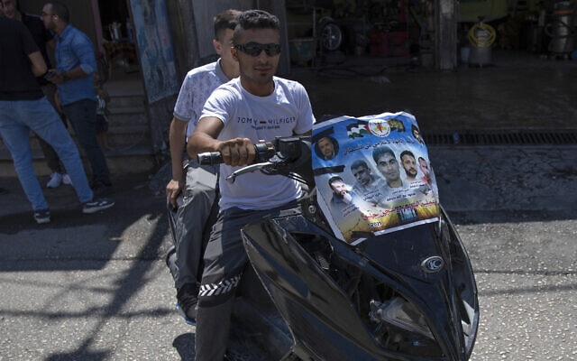 פלסטינים על קטנוע בג'נין עם פוסטר של ששת האסירים שברחו מכלא גלבוע, 8 בספטמבר 2021 (צילום: AP Photo/Nasser Nasser)