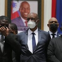 ראש ממשלת האיטי במרכז, על רקע תמונתו של הנשיא שנרצח, יולי 2020 (צילום: AP Photo/Joseph Odelyn, File)