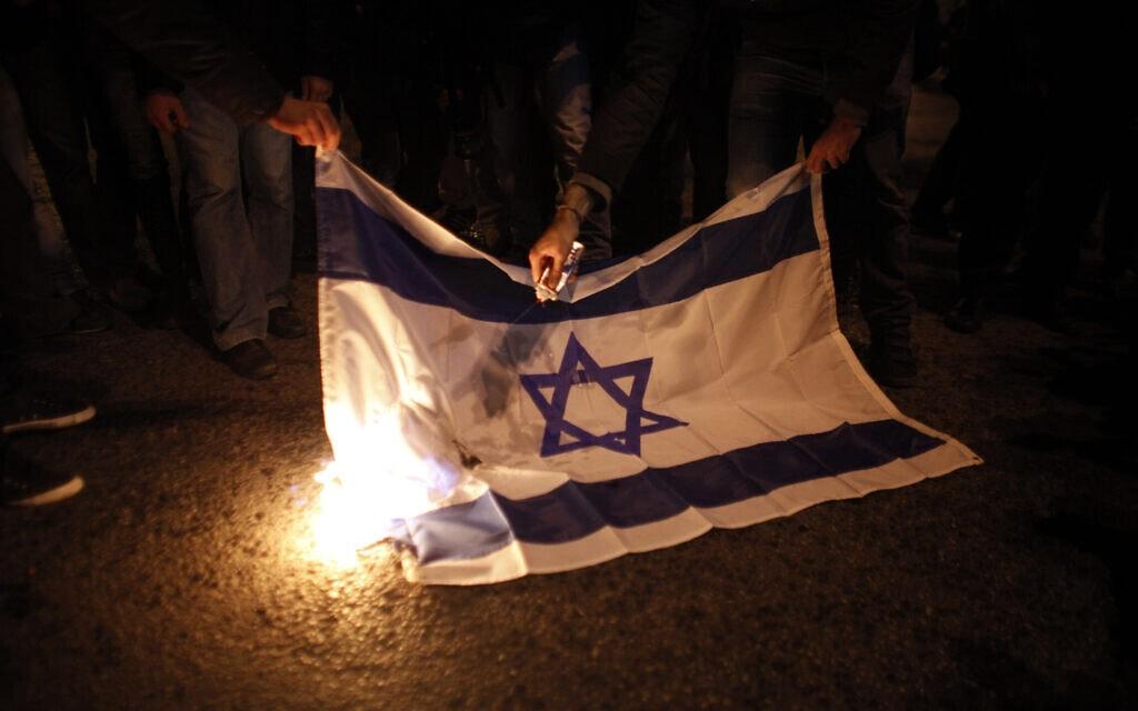 מפגינים שורפים את דגל ישראל מול שגרירות ישראל באתונה, יוון, 17 בנובמבר 2012 (צילום: AP Photo/Kostas Tsironis)