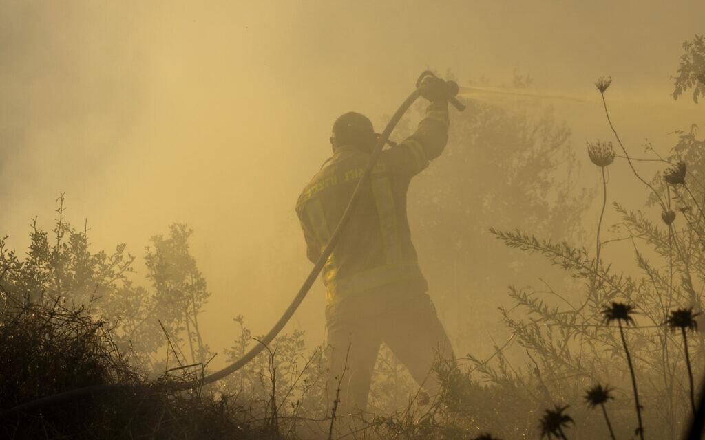 לוחם אש מנסה לכבות את הלהבות בשרפה הגדולה בהרי ירושלים, ליד מושב גבעת יערים, 16 באוגוסט 2021 (צילום: אוליבייה פיטוסי/פלאש90)