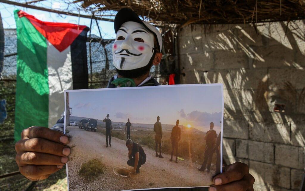 פלסטיני במסיכת גאי פוקס מפגין ליד בית חנון עם תמונה של המחילה שחפרו 6 האסירים שברחו מכלא גלבוע, 6 בספטמבר 2021 (צילום: Atia Mohammed/Flash90)