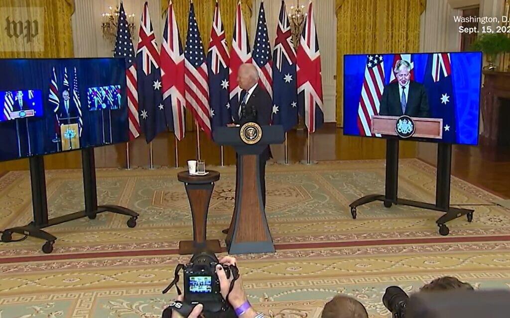 """נשיא ארה""""ב ג'ו ביידן, ראש ממשלת אוסטרליה סקוט מוריסון וראש ממשלת בריטניה בוריס ג'ונסון חותמים על אמנת אינדו-פסיפיק.צילום מסך מסרטון וידאו של וושינגטון פוסט"""