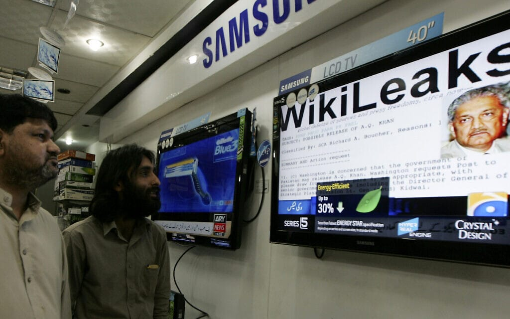 אנשים בקראצ'י, פקיסטן, צופים בתוכנית טלוויזיה על ההדלפה הגדולה של ויקיליס על תוכנית הגרעין הפקיסטנית, 1 בדצמבר 2010 (צילום: AP Photo/Fareed Khan)