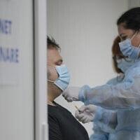 פציינט מקבל את מנת החיסון השלישי נגד קורונה בבית חולים בבוקרשט שברומניה, 4 באוקטובר 2021 (צילום: Vadim Ghirda, AP)