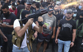 פעיל תנועת אמל השיעית יורה באוויר במהלך הלוויה של אחד ההרוגים במהומות בביירות ב-14 באוקטובר 2021 (צילום: AP Photo/Bilal Hussein)